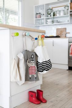 Colourful hooks in a kitchen for hanging grocery bags and other things (via Decor 8).