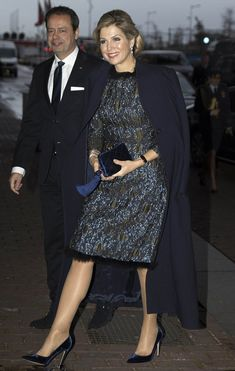 Queen Maxima in shimmery midnight blue gown with a feathered collar with a statement smoky eye, silver drop earrings and a sumptuous velvet clutch bag, as she arrived at the Prince Bernhard Cultuurfonds Awards.