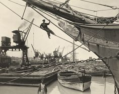 A man sits on a chain while working on a ship in a crowded harbor. Callao, Peru.