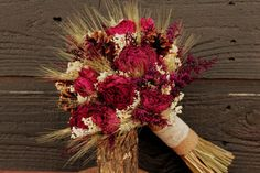 No need to worry about your flowers wilting with this rustic bouquet. The peonies and wheat have already been dried in advance and the pine cones don't require any water at all! | Gorgeous Red Wedding Bouquets