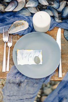 Gold calligraphy written on mussel shell as seating name | Beach wedding table setting in shades of ocean blue | fabmood.com #weddingtable #weddingtablescape #tablesetting #beachwedding #beachtablescape #oceanblue #mistyblue #mistygrey