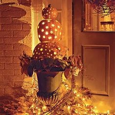 This I have done!  Go to Hobby Lobby, get three pumpkins of different sizes and then take your drill and drill holes in each.  Run lights throughout the pumpkins and then glue them together. Take a grapevine wreath,break it apart so part of it hangs down, add fall garlands and fall picks and light it! Very festive.