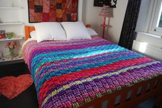 Double bed with a colourful basket weave crochet blanket
