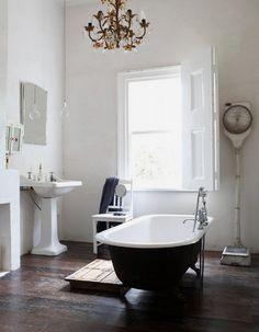 Bañera lacada en negro sobre paredes blancas. La lámpara rococó subraya el espíritu vintage de este baño.