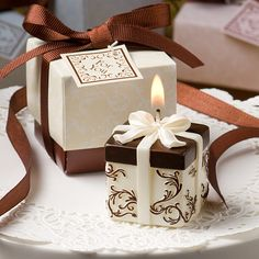 "This attractive ivory and brown Gift Box Collection candle favor makes a gift that's destined to light up your guests' day Talk about a gift that keeps on giving! This little gift box candle is one hot item and it's sure to add a classy and memorable touch to your day. Sold only by Party Supplies Delivered, each Gift Box Collection scented candle favor measures 1.75"" tall x 1.5"" wide and remarkably resembles an exquisitely wrapped gift in a classic chocolate brown and ivory damask design ..."