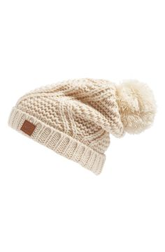 This soft, slouchy beanie with a ribbed turn-up brim is topped with a fluffy pompom for classic cold-weather style.