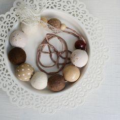 Krajkové ,,Něžné, romantické, krajkové...,, Kuličky potažené látkou, dřevené korálky a plstěné kuličky navlečené na hedvábné stužce. Kuličky jsou uplstěny z nejjemnější vlny - australského merina. Vlna je jemná a neškrábe. Dřevěné korálky jsou potaženy velmi kvalitní látkou na způsob madeirské krajky a látkou s motivem puntíků. Hedvábná šňůrka je z ...