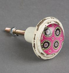 The single knobs in the Modern Marrakech print are a great way to customise your furniture and colour scheme an interior. They are with the Moorish style pink print with a rustic white surround. These knobs are made out of pewter and have a brass rod fo