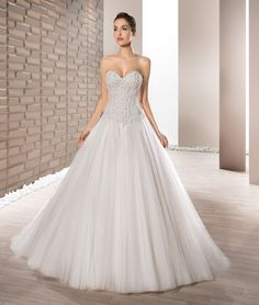 Delicately beaded Venice lace adorns the bodice of this elegant Tulle Ball gown featuring a Sweetheart neckline and Basque waist.  The back is finished with a Lace-up closure and Chapel length train.