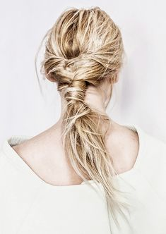 Take full advantage of your snagged, pillow-tousled strands by braiding them in a low fishtail, then securing it in a ponytail at the nape of your neck. Wrap a thick strand of hair around the elastic, pin in place, then pull everything apart. A spritz of texture spray on the ends will complete this messy-chic look!