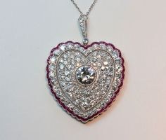 A large Edwardian platinum pendant the outer border set with calibre cut rubies, a border of old cut diamonds, a heart shaped open border, the centre of the heart pave set with old cut diamonds with in the middle an old cut diamond (app. 2.25 carats and app. 8 carats in total), Nehterlands, circa 1910.