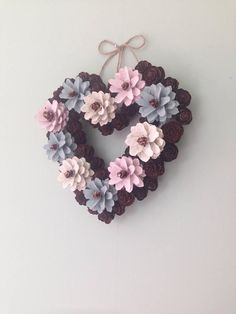 Handcrafted pinecone love heart shaped wreath. Suitable for indoor or outdoor decoration. Pink, duck egg blue and cream with natural pinecones. Each pinecone is handcrafted and individually painted then mounted onto a 20cm base.