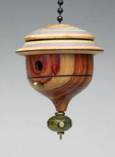 This cute miniature birdhouse ornament is a wonderful addition to your Christmas tree, or a unique fan/light pull for ceiling fans. It comes with a ball chain, so its easy to use either way. Some people prefer to just hang it in a window for ongoing enjoyment. Each one is individually made and unique.  EXTREME ornaments have colors on the roof, and a handmade glass lampwork bead finial on the bottom.  Turned by hand on a lathe, of assorted woods, with a little brass peg for our imaginar...