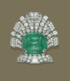 AN ART DECO EMERALD AND DIAMOND BROOCH   Set with a sugarloaf cabochon emerald in a pavé-set diamond palmette surround, with baguette-cut diamond detail, late 1930s, 5.5 cm