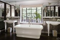 Ann Sacks tiles distinguish the master bath, where a pair of Lefroy Brooks console sinks flank a Waterworks tub; the fittings are also all by Lefroy Brooks.