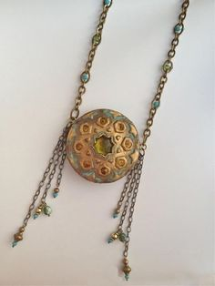 Necklace by ALIZARINA JEWELS | Polymer Clay Planet Love the novel placement of the pendant. The pendant itself is from another time and place. Gorgeous patina. Beautiful shapes. On Polymer Clay Planet http://polymerclayplanet.blogspot.com/2014/10/necklace-by-alizarina-jewels.html