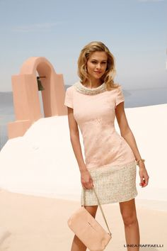 Linea Raffaelli cruise collection 16-17-set056 - dress 161-620-01 nb Helemaal een model van nu deze roze jurk met een rozendessin en een brede strook van een ander materiaal aan de onderzijde. Met het korte mouwtje en de trechterkraag wordt terug gegrepen naar de zestiger jaren stijl.