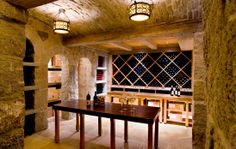 Amazing basement wine cellar with plenty of storage and a wooden tasting table  SLC INTERIORS - Interior Design - Weston Country Estate Wine Cellar