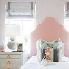 doll on blush pink headboard