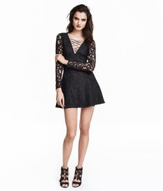 Short, gently flared lace dress with a V-neck with decorative lacing at front. Concealed back zip, long lace sleeves, and  jersey lining.