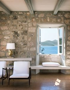 Looks like a beach cottage in Greece. Liking the exposed stone and wood beams, and window seat.