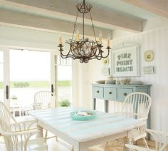 Classic beach cottage living. blue and white. Rustic wood... and the wire chandelier holds beach treasures.