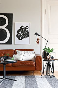 Living room decor with a cognac leather couch. My favorite part of this setup? The little toy monkey hanging from the lamp.