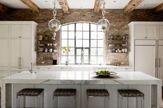 Two glass pendant lights hang above a spacious island with a marble waterfall countertop, creating a stunning focal point in this charming kitchen. Exposed brick walls lend character to the space, and white cabinetry keeps the room feeling fresh and bright.