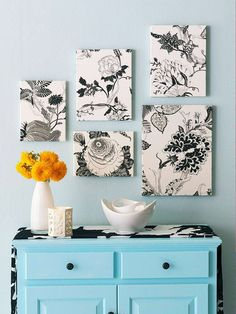 Patterned fabric stretched over canvas frames, hung on one wall in a cluster.