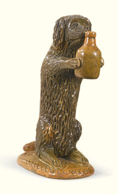 est $20,000-$30,000 Rare glazed red earthenware upright dog holding a jug, Samuel Bell or Solomon Bell (act. 1834-1882)Strasburg, Shenandoah County, Virginia, Visual Grace: Important American Folk Art from the Collection of Ralph O. Esmerian