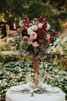 Tall centerpiece idea with rich red tones, blush roses and messy greenery.
