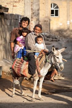 An elderly man, a young man, a small girl and an infant sit on a grey donkey. Photo taken on August 26, 2007 in Kaj, Chaharmahal and Bakhtiari Province, Iran.