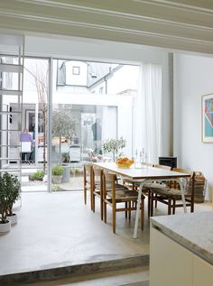 The view from the kitchen is as lively as it is light, taking in the dining area, tiny courtyard garden, and the separate office building backed by the jumble of old buildings to the rear. The rustic dining chairs are by Börge Mogensen from Karl Andersson & Söner. Photo by Mark Seelen.