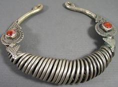 Antique non-precious metal torque from Pakistan ( Swat ? ). | Great design ringed in spiral spring using only one big metal thread. Embellsihed with two cornelians or agate stones on the center of a lotus flower ( very old representation, back to the 7th century ). | First half of 20th century.