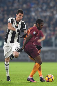 Mario Mandzukic (L) of Juventus FC is challenged by Gerson of AS Roma during the Serie A match between Juventus FC and AS Roma at Juventus Stadium on December 17, 2016 in Turin, Italy.