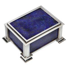 An exquisite Sterling silver and Blue Lapis enamel Art Deco box, for cigarettes or trinkets, the four reeded corners terminating in stepped feet, the front, sides and lid with deep blue enamelling, the interior lined with sycamore and the inside of the lid gilded for contrast. Bearing hallmarks for Richard Comyns, London, c1935.