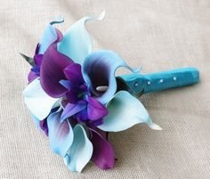 This is a beautiful bouquet made with the most realistic flowers available. So amazing to the touch that people wont be able to tell they are not real! Beautiful Floramatique Purple with Blue Edges Callas, Aruba Callas, Purple Callas and Two Tone Purple/Blue Orchids. The bouquet is 7 Wide. Each Calla Lily Measures about 3 Tall x 2 1/4 Wide. The last is a picture of someone holding this size bouquet just for reference.  Perfect for Small Weddings of Bridesmaids. It will be finished w...