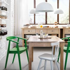 A kitchen with a table and sideboard in solid birch and chairs in green and white