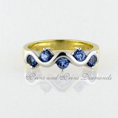 There are 5 = round cut tanzanite's half tube and claw set in an yellow and white gold two-tone band Tanzanite Rings, Tanzanite Stone, Gemstone Rings, Rose Gold Ring Set, Wave Design, African Jewelry, Eternity Ring, Wedding Bands, Heart Ring