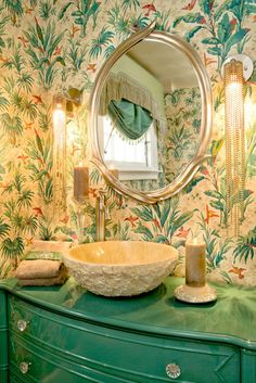 I die - Glossy green paint, a stone sink, a vivid wall covering and dangling bead wall sconces all combine to create a vanity that would really wake you up each day.