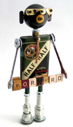"""""""Robama Redux""""   Height: 12.5""""   Principal Components: Tobacco tin, pool ball, sash lock, wrenches, Scrabble tiles, rubber letter stamps, hose fittings, springs, clock gear"""