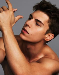 Nolan Funk shirtless with his hands raised