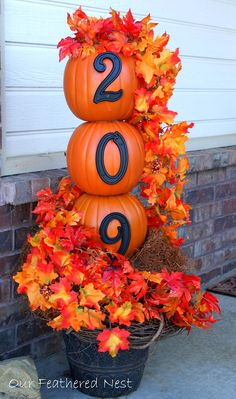Faux pumpkins are the perfect shape for stacking. Add a personal touch by adding your house numbers to this adorable topiary. See more at Our Feathered Nest »  - GoodHousekeeping.com