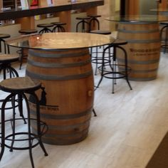 Wine barrel cocktail tables in the office. Love this idea wine corks also fill the top under the glass