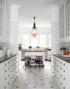 love the balance & symmetry.  subway tile with dark grout taken above eye level, ROWS of drawers with bin pulls and cabinets, shallow counter, vintage light...turn of the century orderliness!