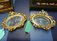 Pair of Hollywood Regency glass dishes with gold bird and flower garland decoration.