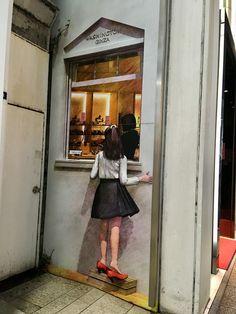 だまし絵の中に住んでいる、赤い靴の女の子。銀座ワシントン靴店の側面の壁画。