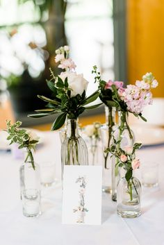 Garden blooms in bud vases paired with botanical table numbers | Caroline Lima