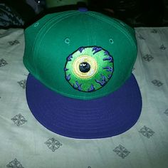"""Mnwka Mishka green eyeball monster snapback hat The hat is green, the rim is purple. The eyeball is green with yellow colored irises and purple veins. The underside of the rim features an open mouth with fangs. The design is called, """"keep watch"""". Mnwka Accessories Hats"""