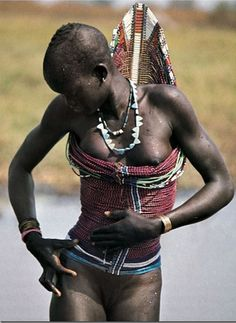 Dinka woman wearing a beaded corset. These corsets, supported by two ridged wires at the spine, are sewn tightly in place at the front and there they will remain until they are cut open - which, for a woman, is on the occasion of her marriage. Photo by Angela Fisher and Carol Beckwith. Text from Angela Fishers, Africa Adorned book.Beautiful!!